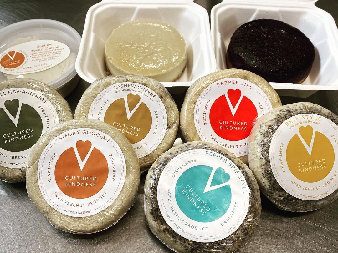 A photo of an assortment of Cultured Kindness cashew cheese rounds and cheesecakes in takeout containers