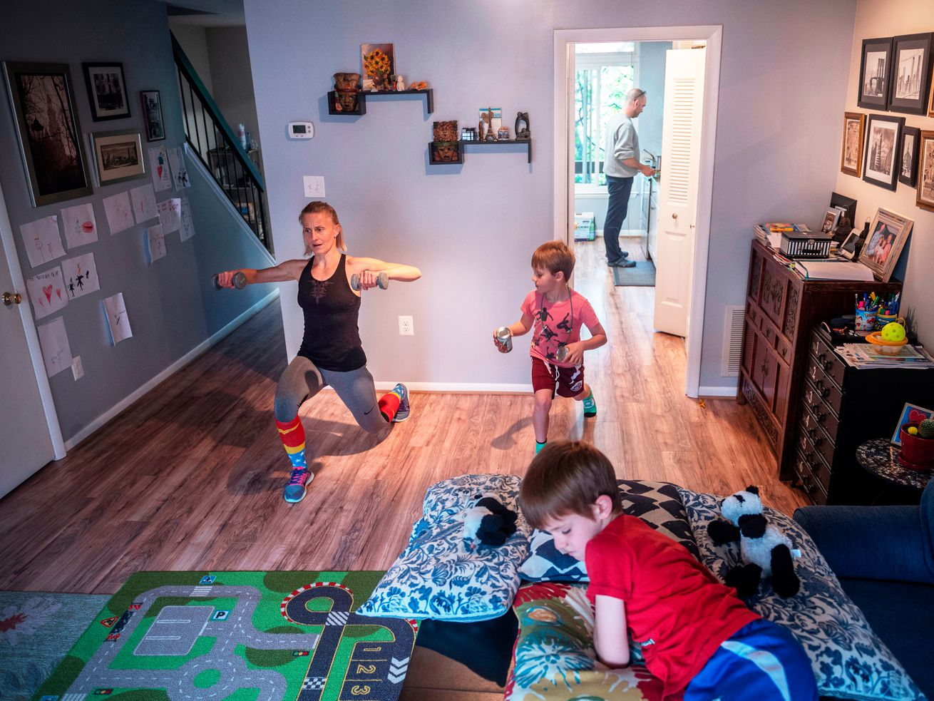 A woman in a yoga pose in her home with her two children and partner visible in the frame.