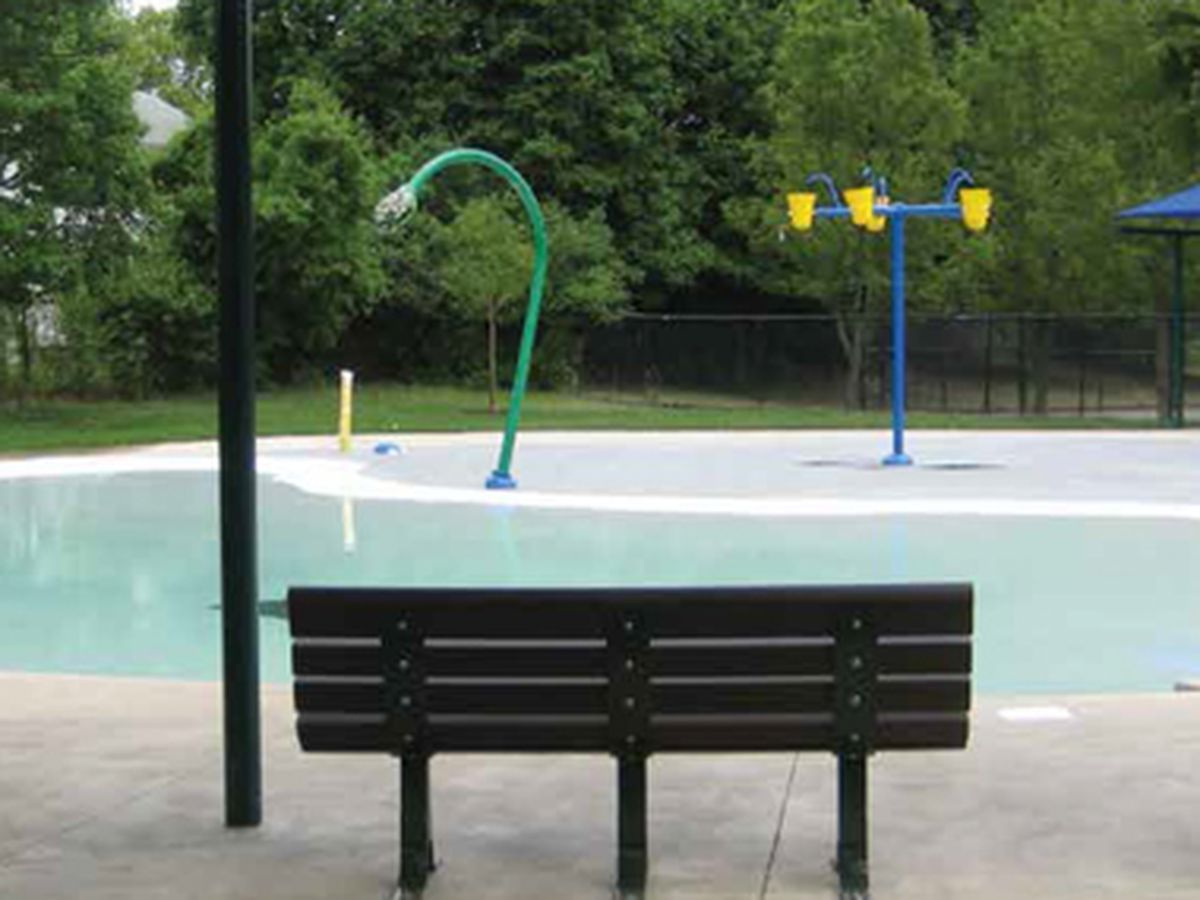 An outdoor pool. There is a bench in the foreground facing the pool.