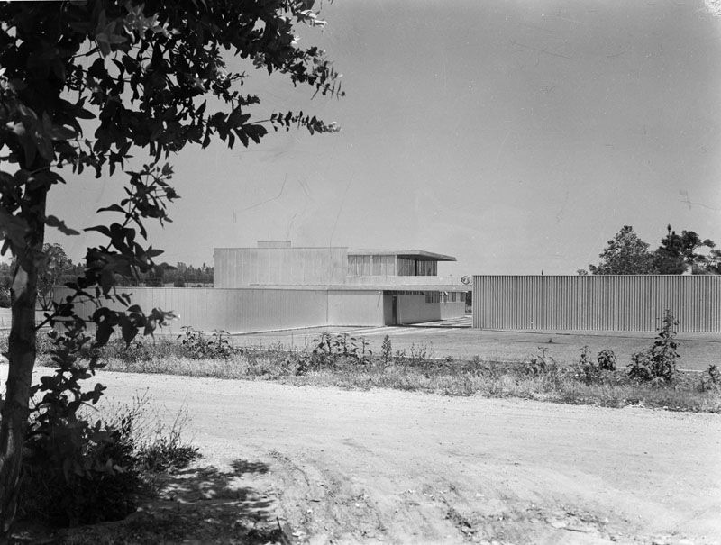 A house with a flat roof. There is a fence next to the house. There is a lot and trees outside of the house.
