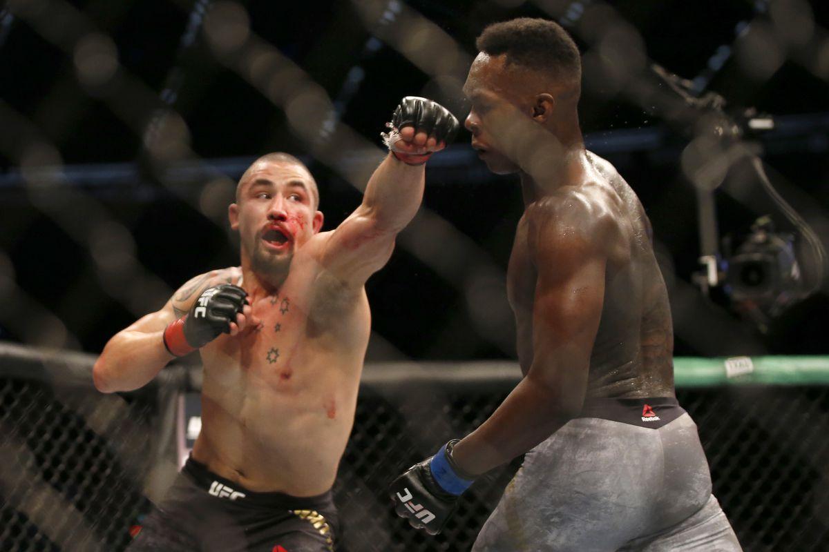 Robert Whittaker lands a left hand on Isreal Adesanya at UFC 243.