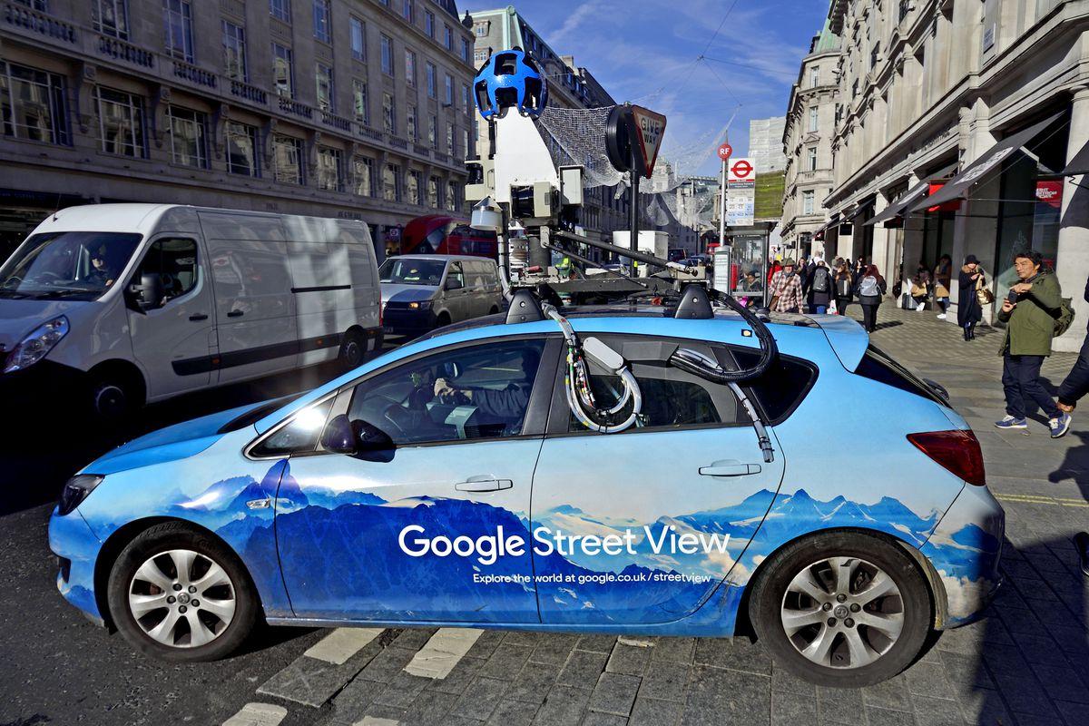 A Google Street View car navigates a crowded street.