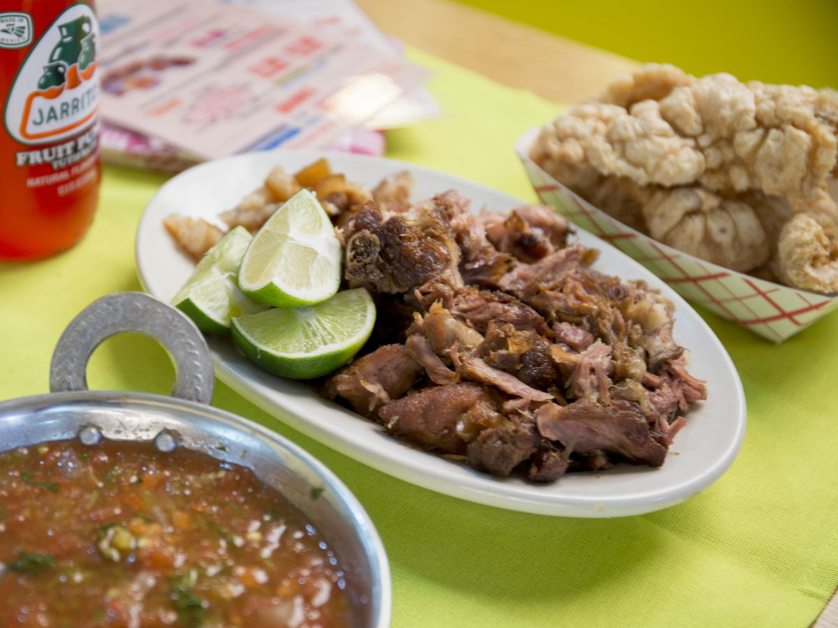 A table laid with large dishes of carnitas