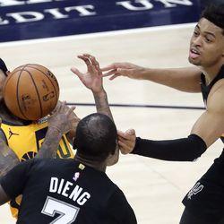 Utah Jazz guard Jordan Clarkson (00) keeps the ball away from San Antonio Spurs center Gorgui Dieng (7) and San Antonio Spurs forward Keldon Johnson (3) during an NBA game at Vivint Smart Home Arena in Salt Lake City on Monday, May 3, 2021. The Jazz won 110-99.