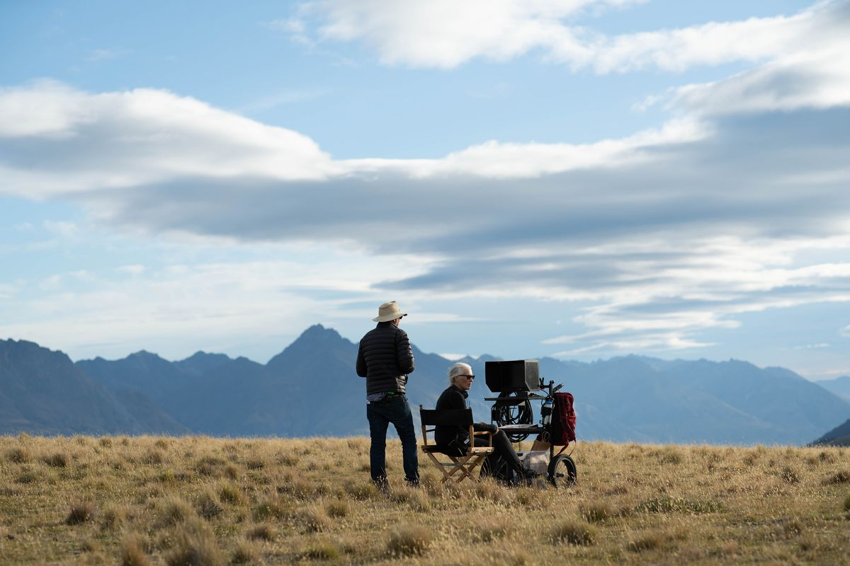 A director behind a camera with an assistant nearby against a mountainous landscape.
