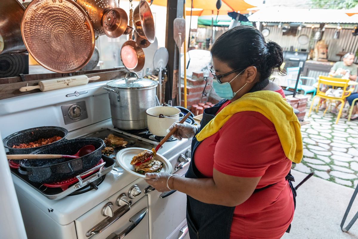 Lucy Silva cooks at her home restaurant Barra de Pan's outdoor stove with copper pans hanging over.