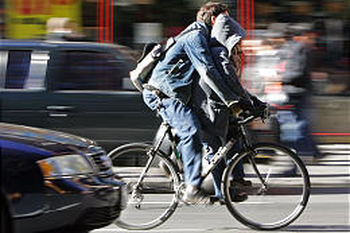 Two people ride a bicycle up the 8th Avenue in New York City. Police records show 21 cyclists have been killed in the city this year.