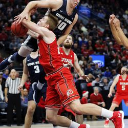 Utah State Aggies forward Quinn Taylor lands on Utah Utes forward Tyler Rawson and fouls him during NCAA basketball at Vivint Smart Home Arena in Salt Lake City on Saturday, Dec. 9, 2017.
