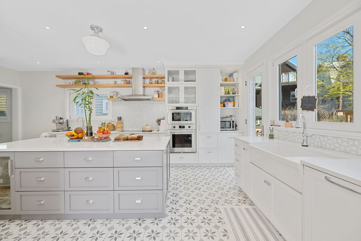 A kitchen with a large island, grey and white tiles, and white cabinetry.