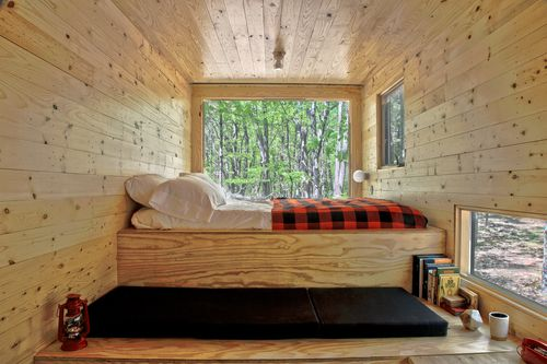 A bedroom in a wooden cabin. There is a bed with a red plaid blanket. There are multiple windows.