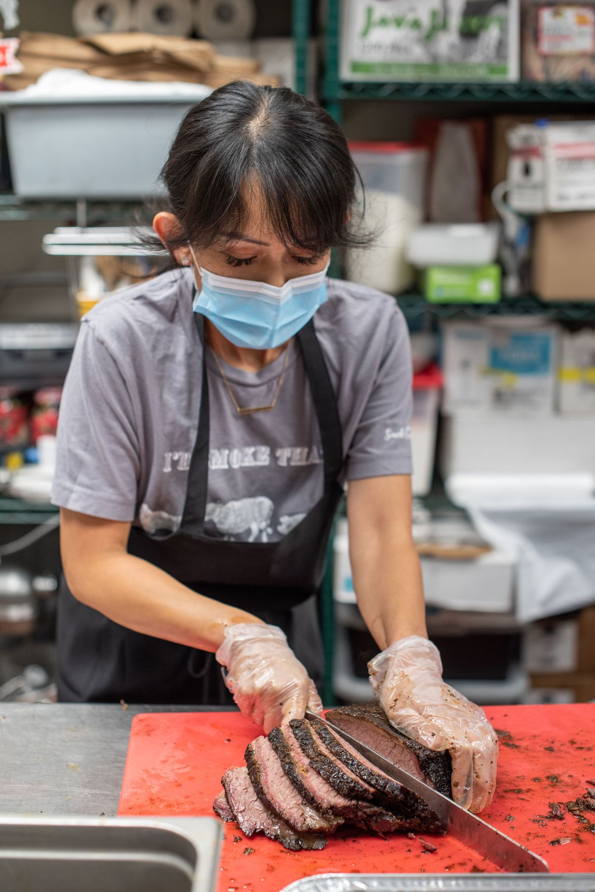 A woman in a blue mask cuts thick slices of brisket on a red cutting board.