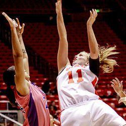 Utah's Taryn Wicijowski, right, shoots over TCU's Eboni Mangum as the University of Utah leads 39-31 against Texas Christian University at the Huntsman Center in Salt Lake City on Wednesday. TCU won 105-96 in quadruple overtime.