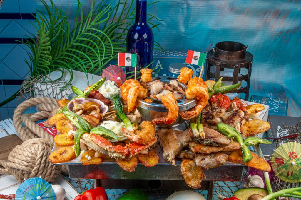 A platter of seafood, including shrimps, crab legs, plantains, and other accompaniments, set in front of a nautical scene of decorations