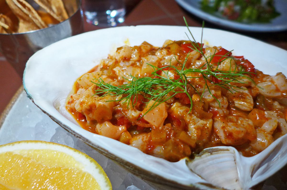 A clam shell of minced seafood in red sauce.
