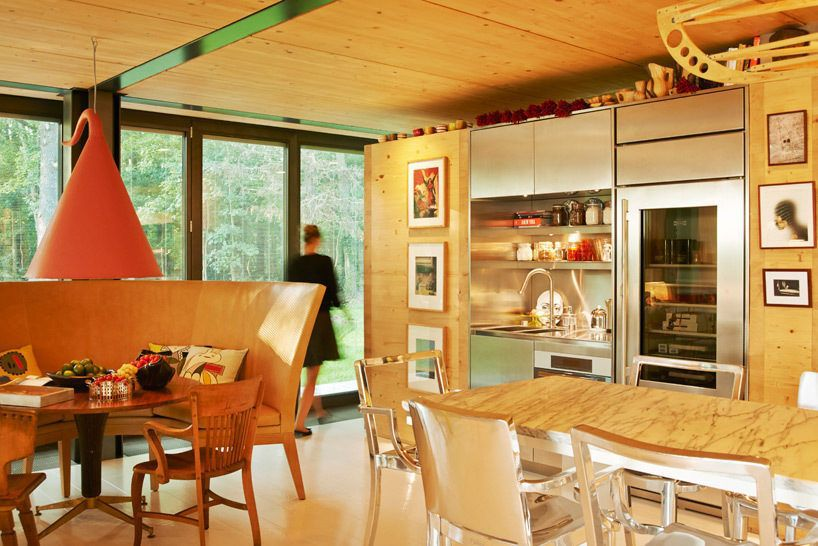 A dining area with a table, chairs, kitchen, and light. The ceiling and cabinetry is wooden.