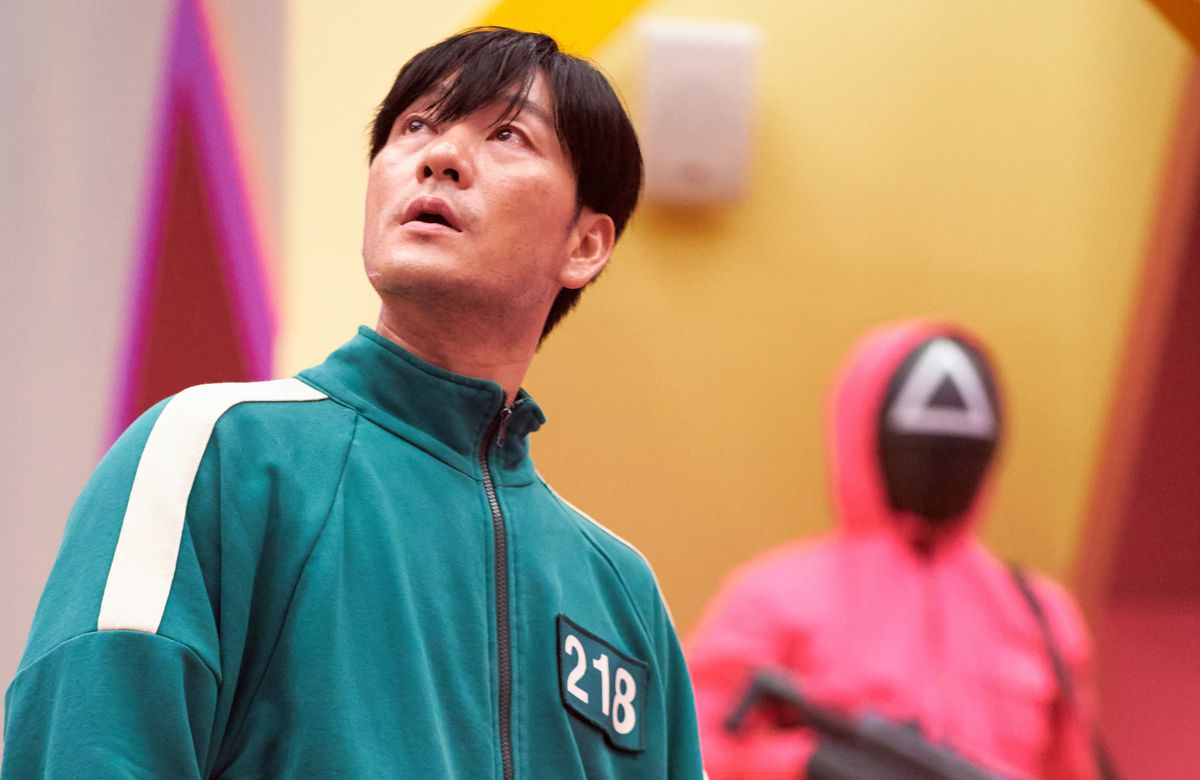 Failed businessman Cho Sang-Woo looks around a Squid Game room while an armed, pink-jumpsuited soldier stands behind him
