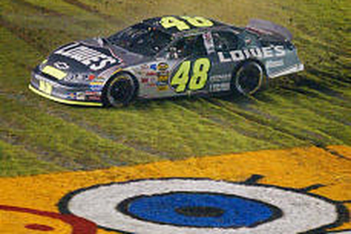 Jimmie Johnson slides through the grass next to the front stretch as he celebrates his win Saturday.
