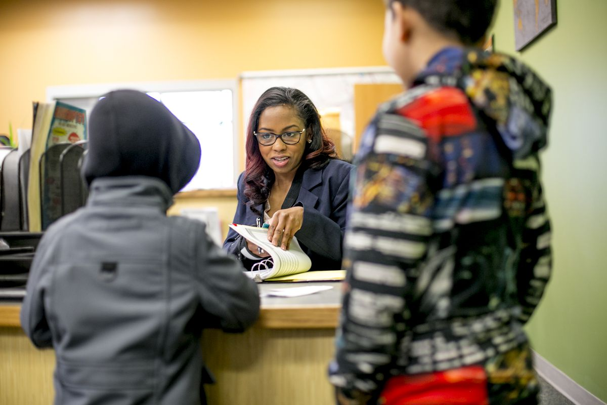 Attendance agent Amanda Bowman signs in students who arrive late for class at Earhart Elementary Middle School in southwest Detroit. She believes her policy of requiring late arrivals to get a tardy pass before they can go to class has improved attendance because it lets her interact with students.