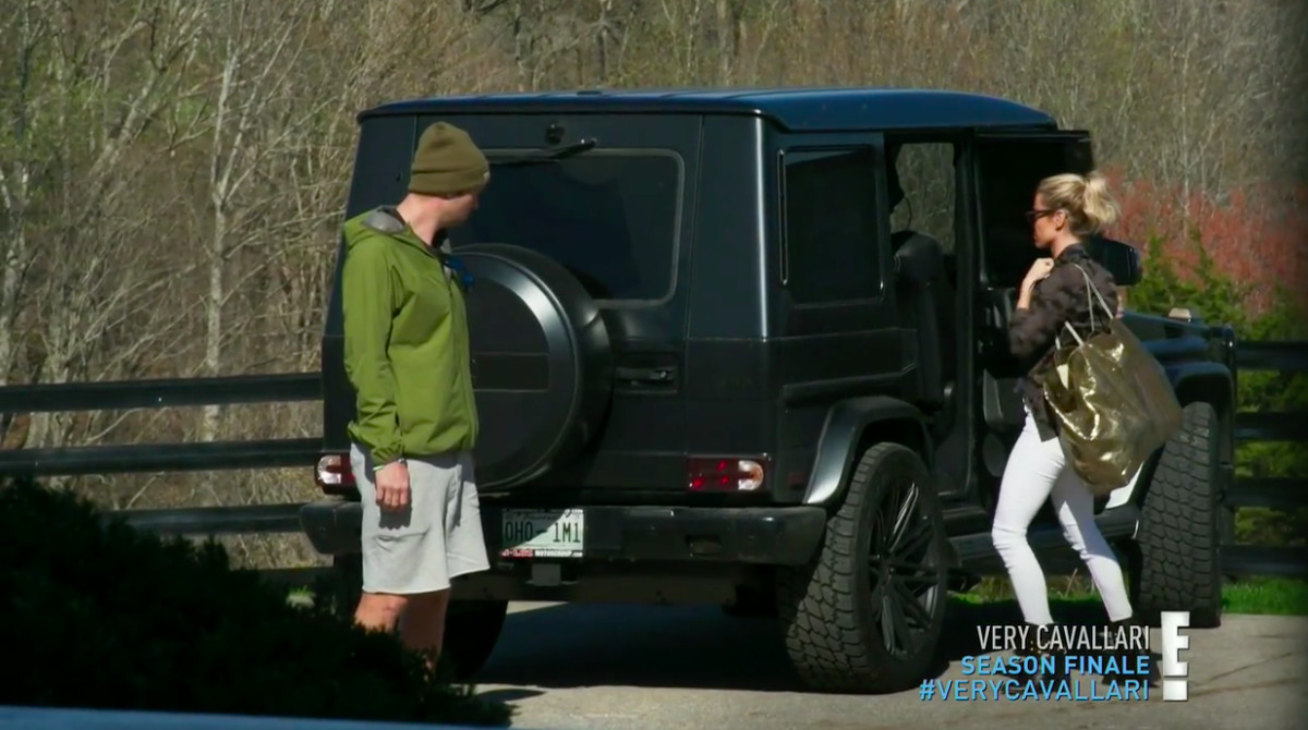 Jay Cutler standing behind his black Jeep wearing a green winter hat, a green windbreaker, and gray shorts