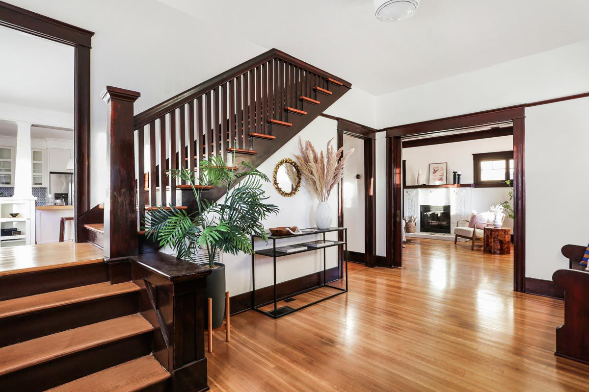 A wood staircase anchor's the home's entryway and connects the foyer, living room, and kitchen.