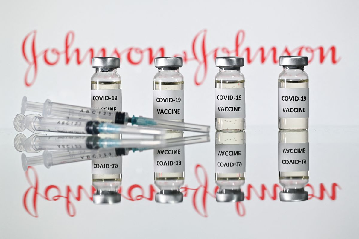 Vials of Johnson & Johnson's Covid-19 vaccine in front of the pharmaceutical company's logo.