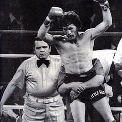 """Danny """"Little Red"""" Lopez leaps for joy as he is hugged by a friend after retaining his featherweight championship title by stopping Ghana's David Kotei in 1978. Refereeing the bout, which was a preliminary to the Muhammad Ali vs. Leon Spinks heavyweight championship, is Ray Solias. Although Lopez, now 57, will be inducted into the Hall of Fame June 13, he works a construction job to support his family financially."""