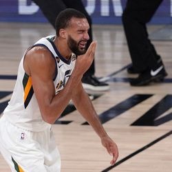 Utah Jazz's Rudy Gobert (27) reaches up after being hit in the face during play against the Denver Nuggets during the second half an NBA first round playoff basketball game, Tuesday, Sept. 1, 2020, in Lake Buena Vista, Fla.