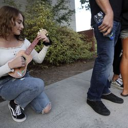 "Natasha Owen plays the ukulele while waiting in line for ""American Idol"" auditions outside of the Northwest Community Center in Salt Lake City on Thursday, Aug. 29, 2019."