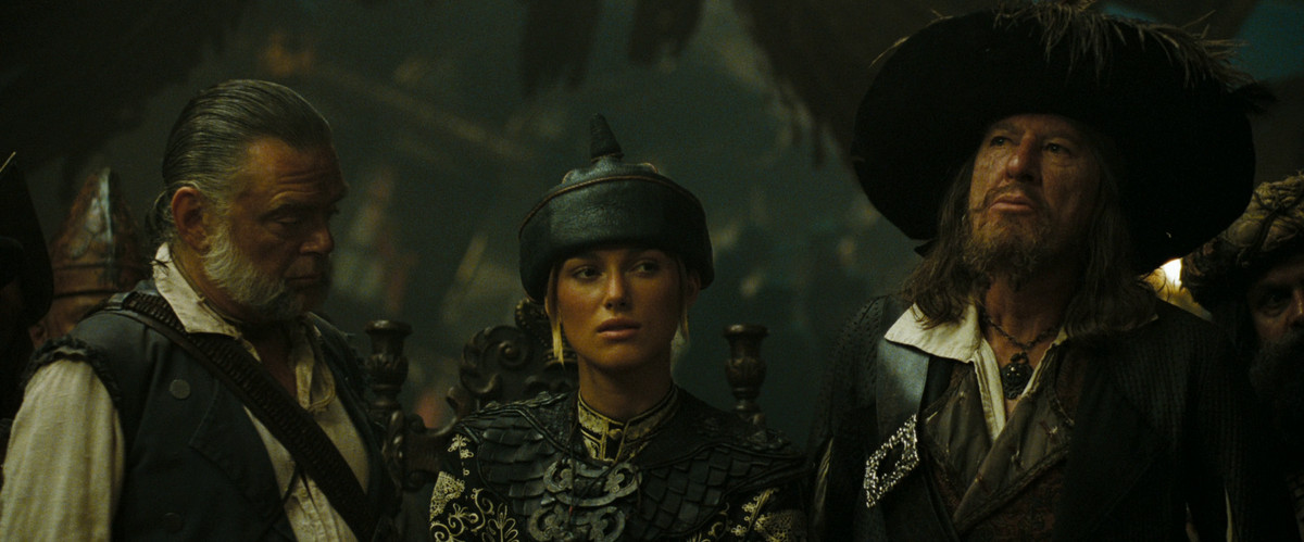 Gibbs (Kevin McNally) Elizabeth (Keira Knightley) and Barbossa (Geoffrey Rush) sit at the Court of the Brethren