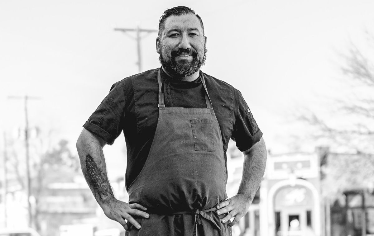 Black and white image of Gustavo Romero from the torso up, hands on his hips, wearing a chef coat and an apron. A corn cob tattoo is visible on his forearm.