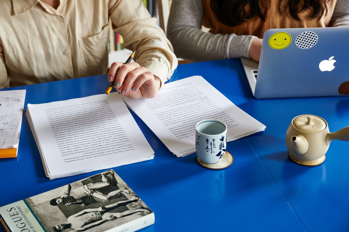 Two people sit working at a bright blue painted table. One person is typing on a laptop which is open. The other person has a pencil and two stacks of paper with text printed. There is a book, a tea kettle, and a tea cup on the table.