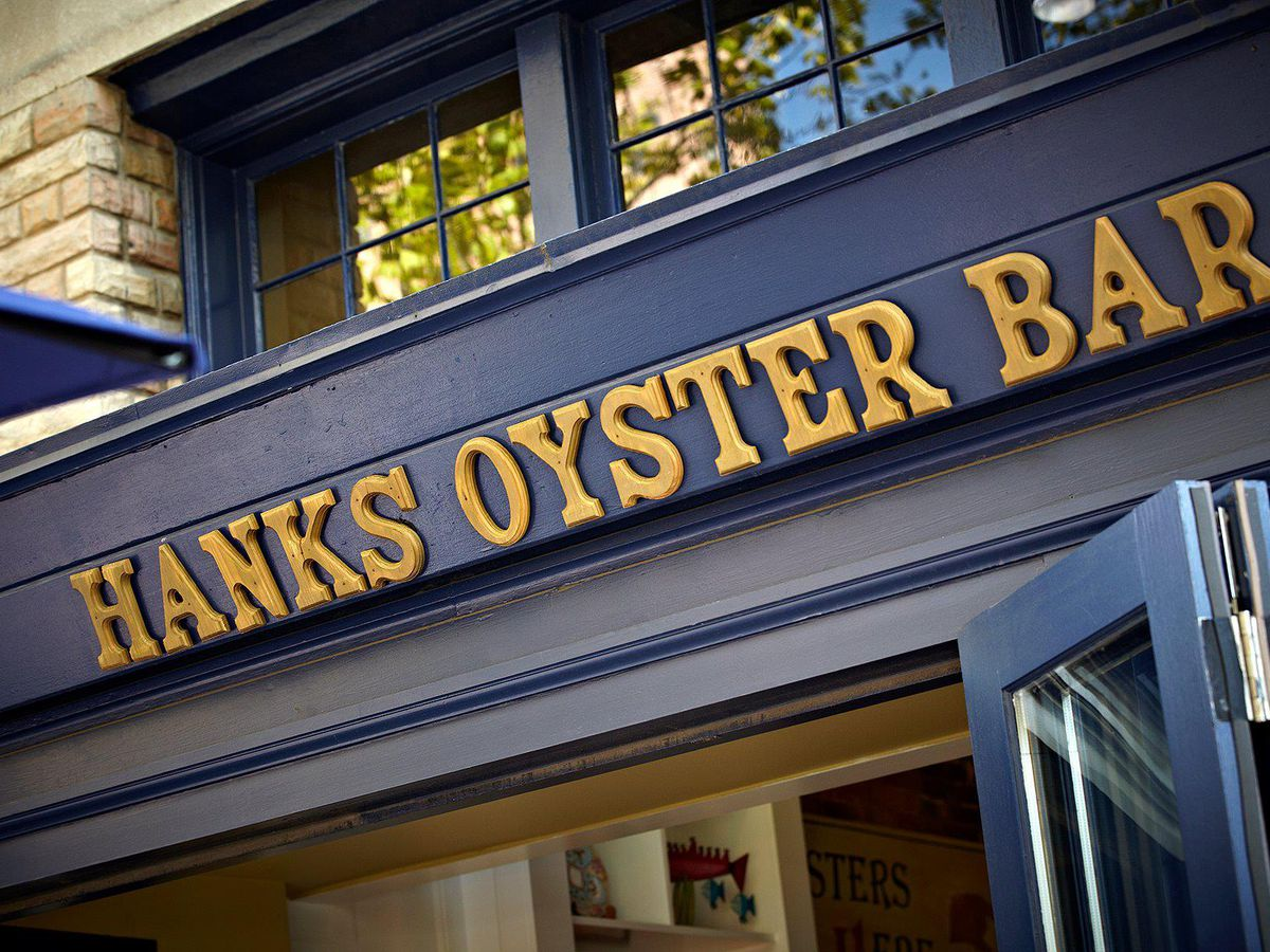 Hank's Oyster Bar's blue signage with golden lettering