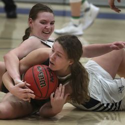 Syracuse's Rachel Godfrey reaches over Davis' Phoebe Arnold as they battle for the ball during a game at Syracuse High School on Tuesday, Feb. 9, 2021.