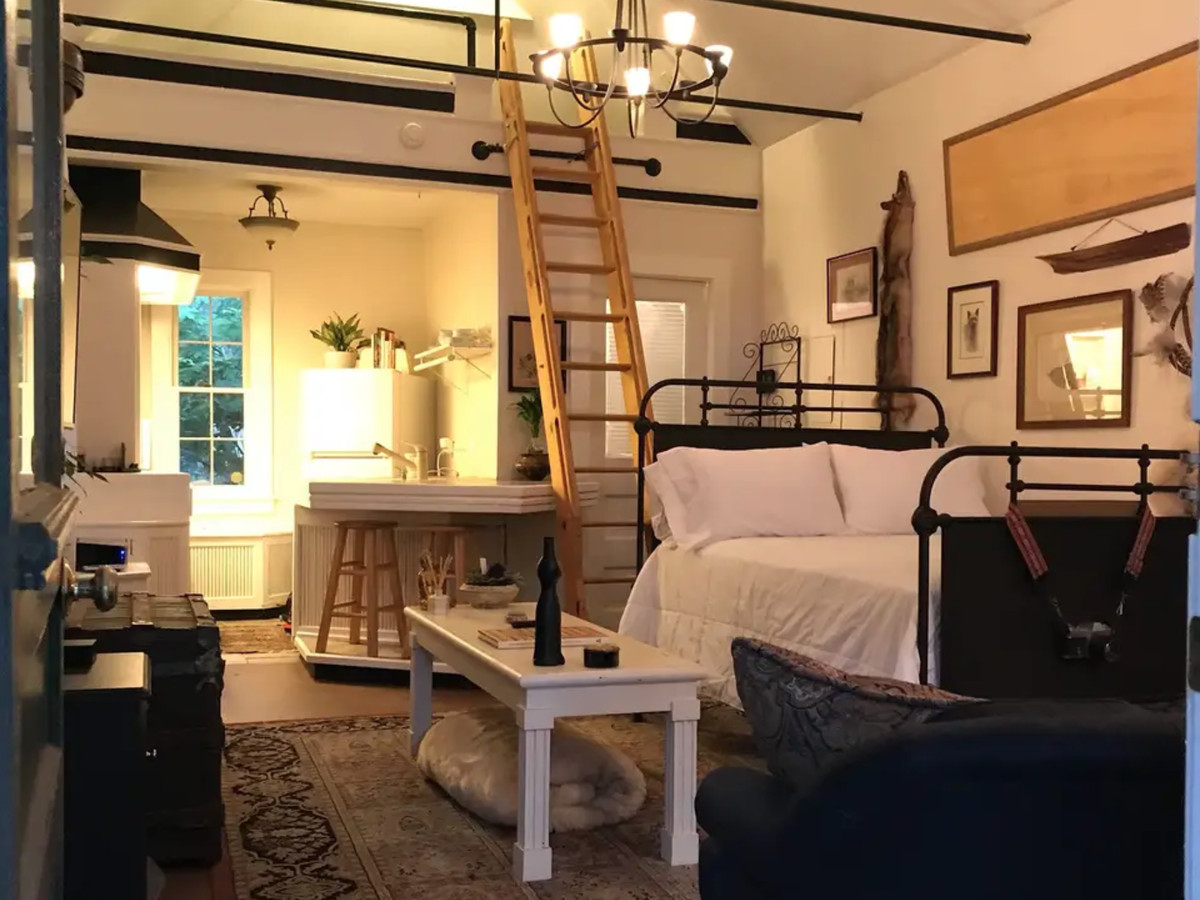 Small room with bed, table and a ladder leading to a window.