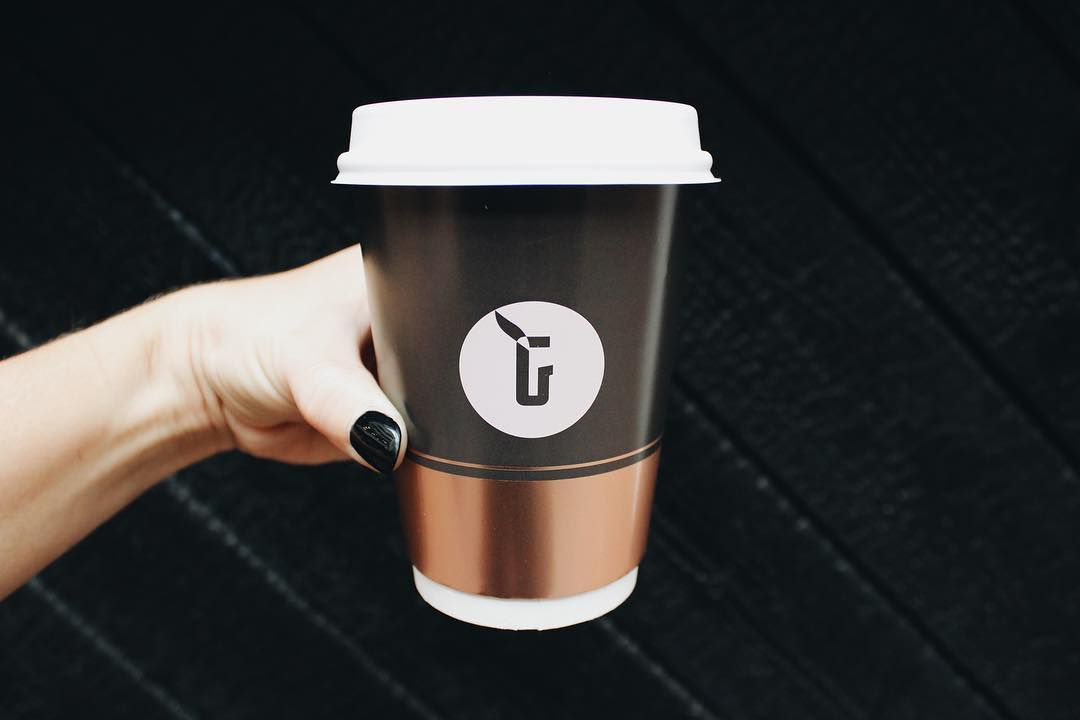 A manicured hand holds a black to-go coffee cup with a copper band around the bottom of it