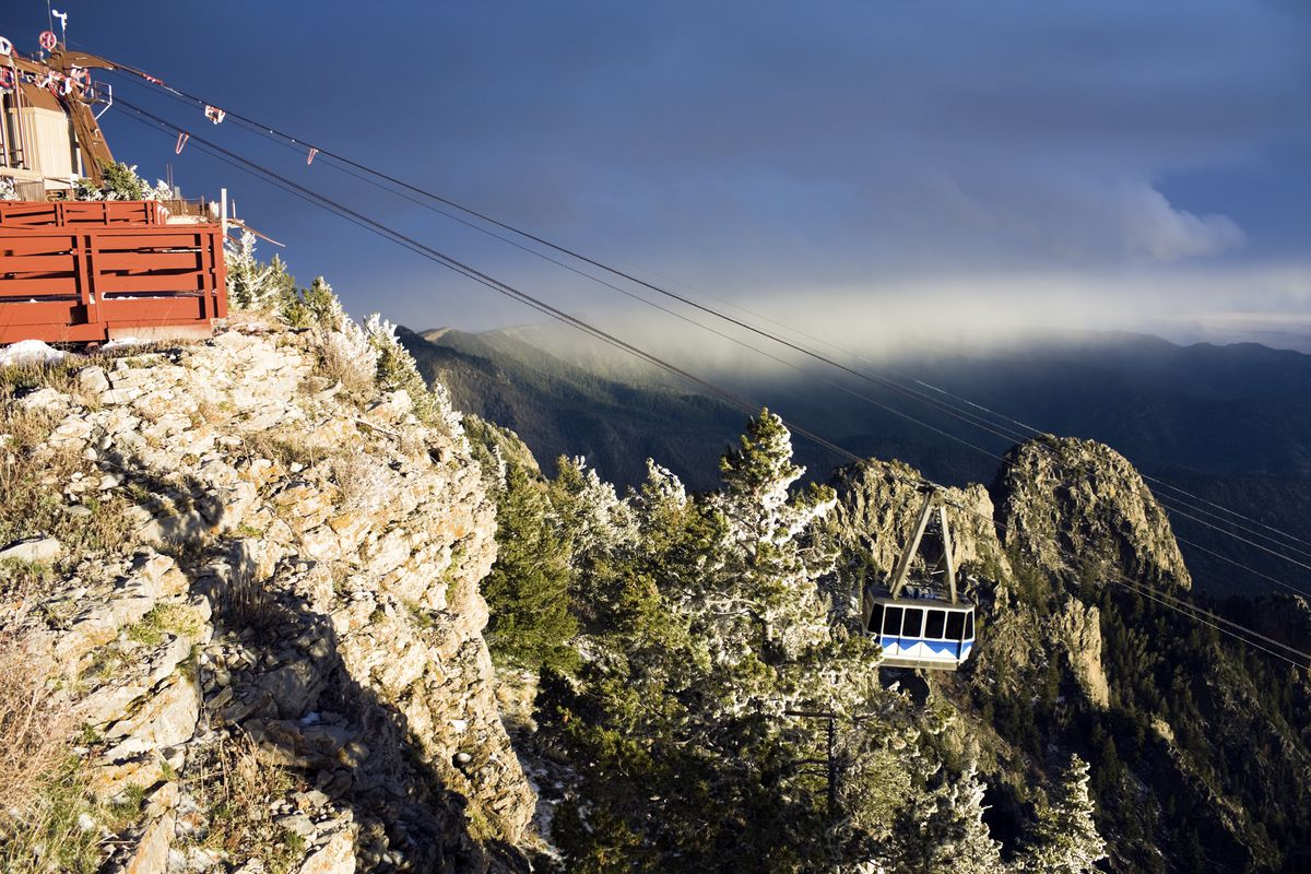 An aerial view of the Sandia Peak Tramway. The tram is white and blue and suspended over mountains with trees.