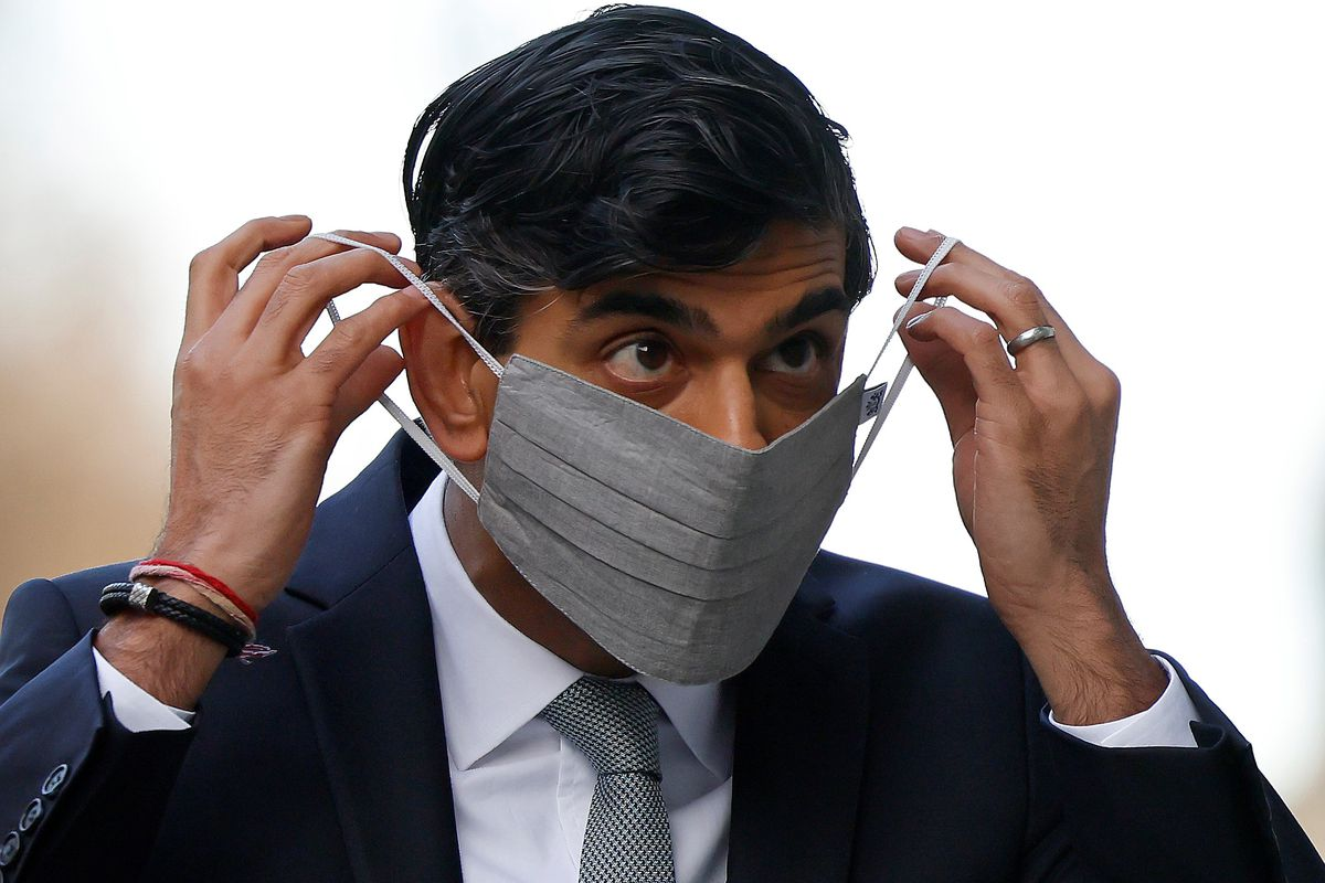 Rishi Sunak puts on a face covering outside while wearing a suit