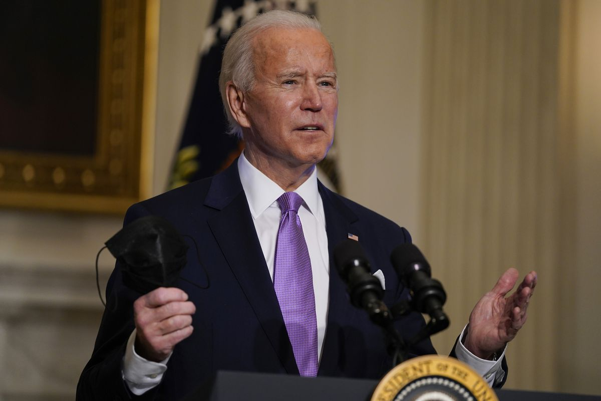 In this Jan. 26, 2021, photo, President Joe Biden holds his face mask as he speaks on COVID-19, in the State Dining Room of the White House in Washington.