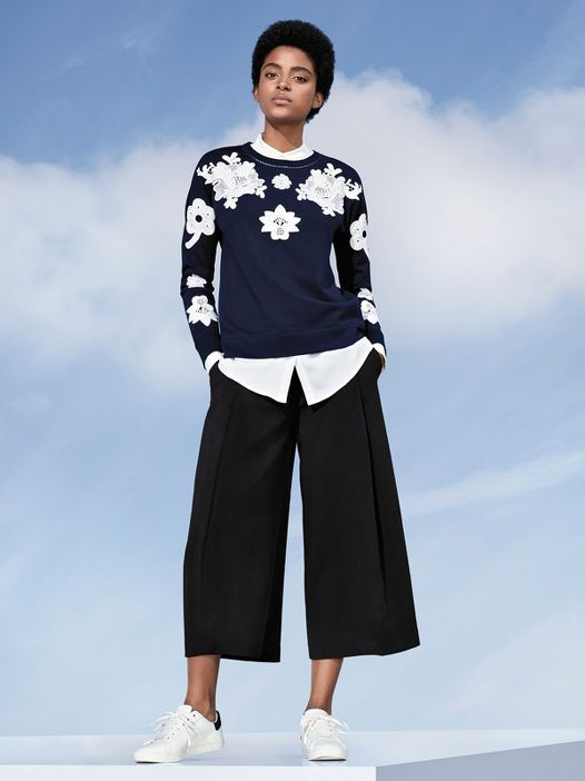 Model in sweatshirt and black wide leg pants.