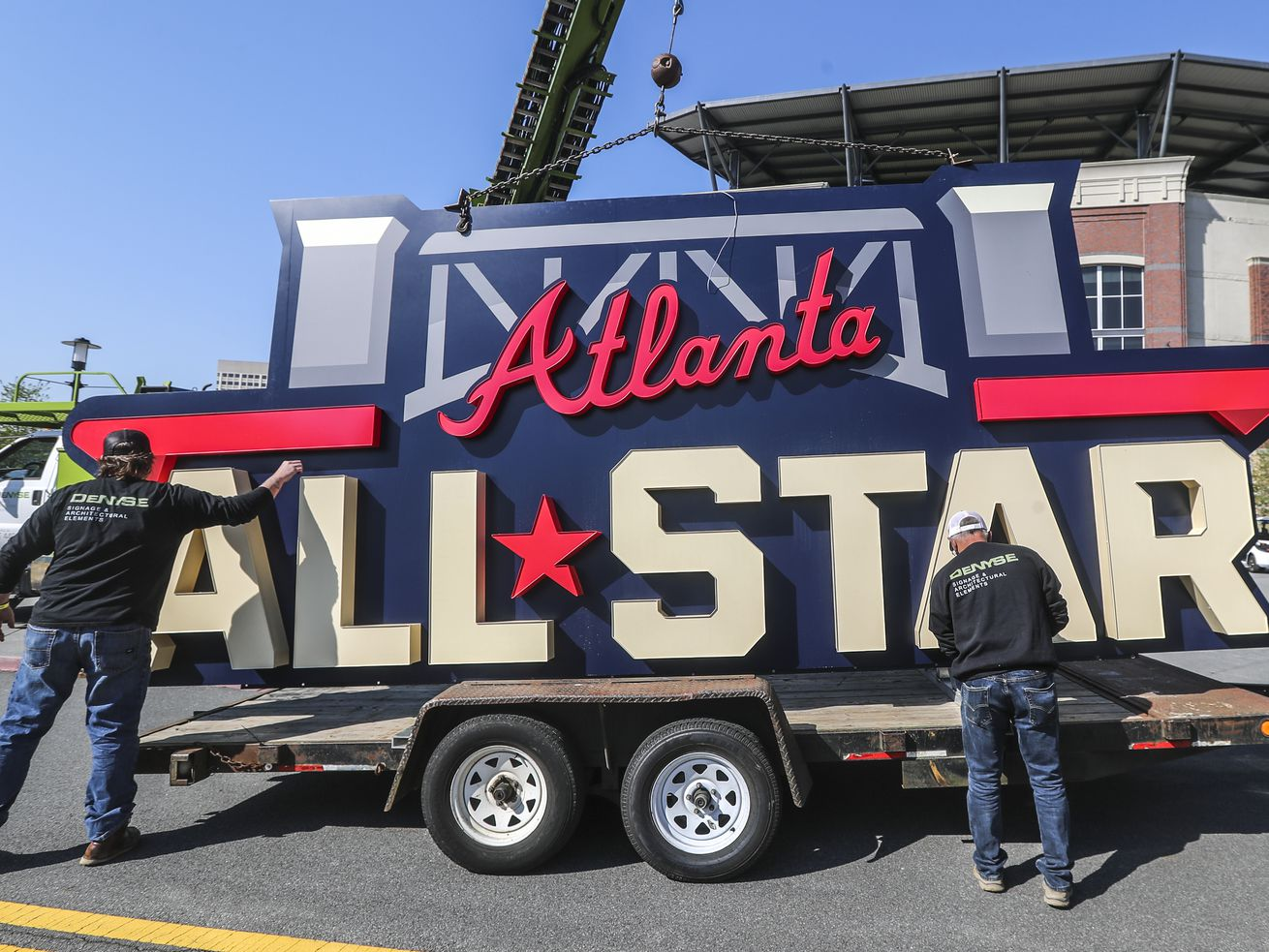 Workers load an All-Star sign onto a trailer after it was removed from Truist Park near Atlanta.