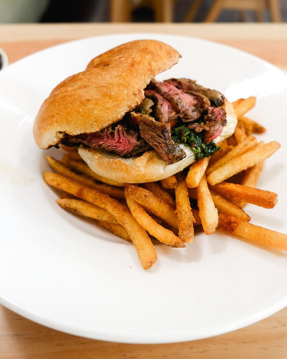 Lomito sandwich with sliced beef topped with salsa criolla and chimichurri aioli and surrounded by classic cut French fries