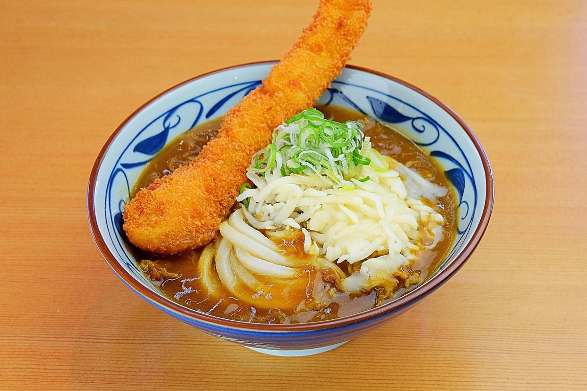 A bowl of udon in broth, garnished with a tempura shrimp