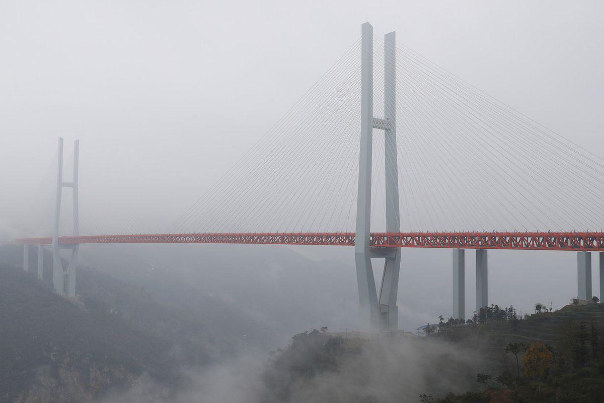 A bridge cloaked in fog rises above rugged terrain.