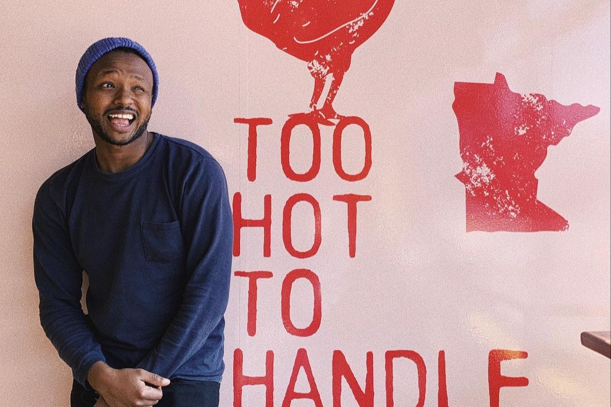 """Nashville Coop's co-owner reclined against a pink wall with red stamped lettering that says, """"Too hot to handle,"""" with an outline of a chicken and an outline of Minnesota"""