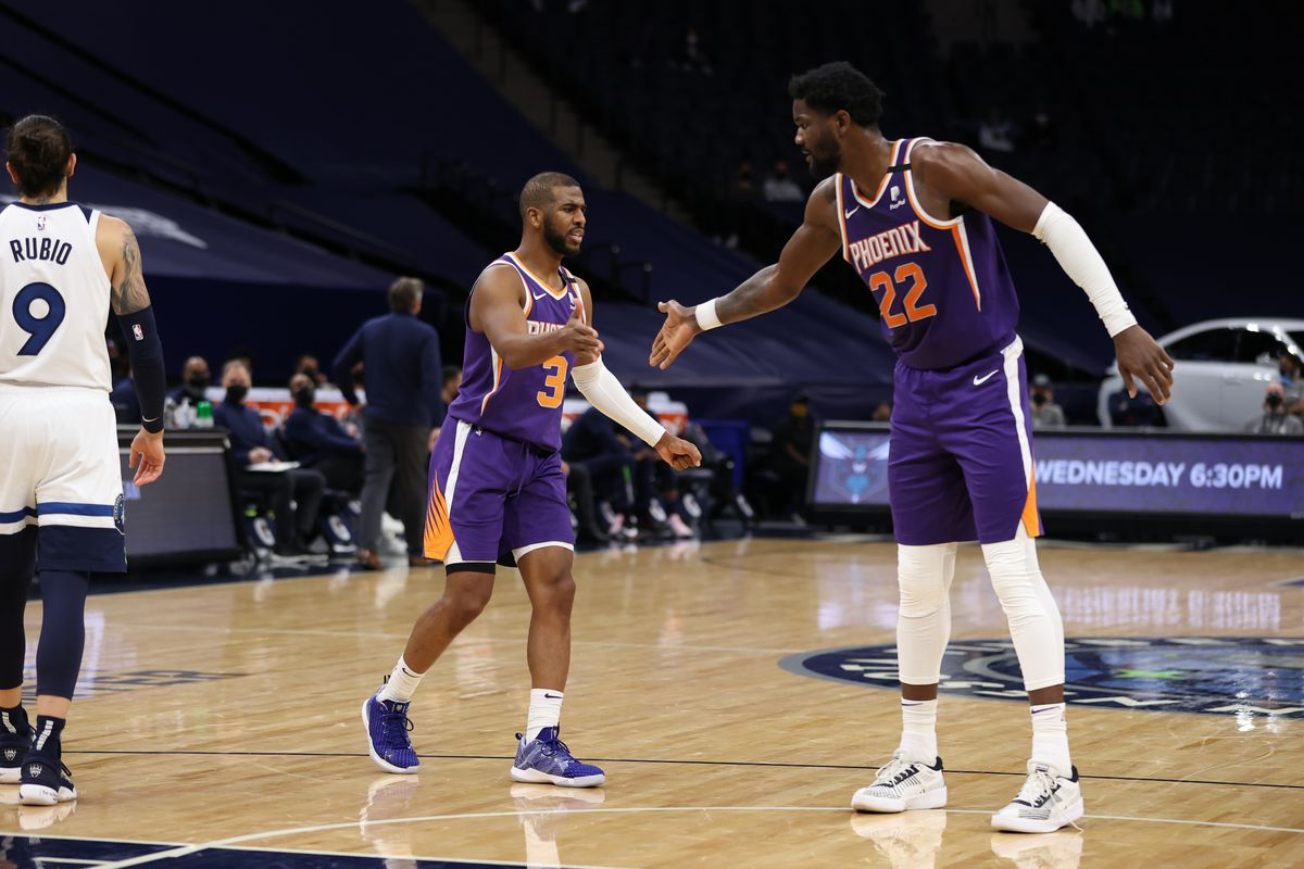 Chris Paul hi-fives Deandre Ayton of the Phoenix Suns during the game against the Minnesota Timberwolves on February 28, 2021 at Target Center in Minneapolis, Minnesota.