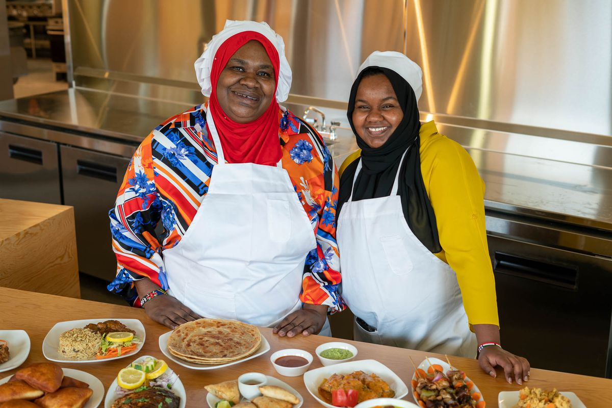 Mwana Moyo and Batulo Nuh of Moyo Kitchen standing behind a table with some of their Somali-Kenyan-Tanzanian dishes.