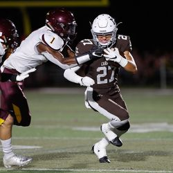 Mount Carmel's Tony Livermore (27) runs with the ball during the game against Montini.