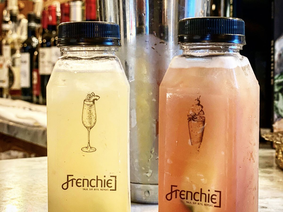 Two plastic bottles of cocktails, branded with the restaurant name Frenchie, sit on a bar