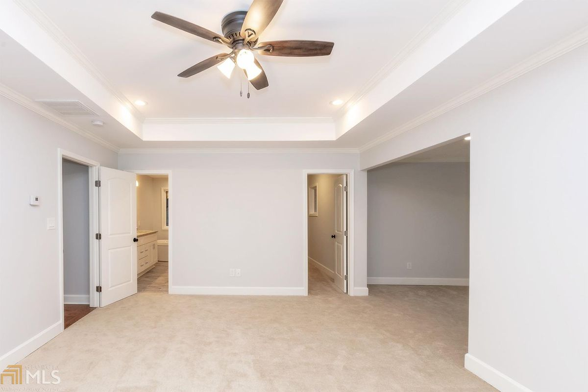 Bedroom with white walls, carpet, tray ceiling and ceiling fan.