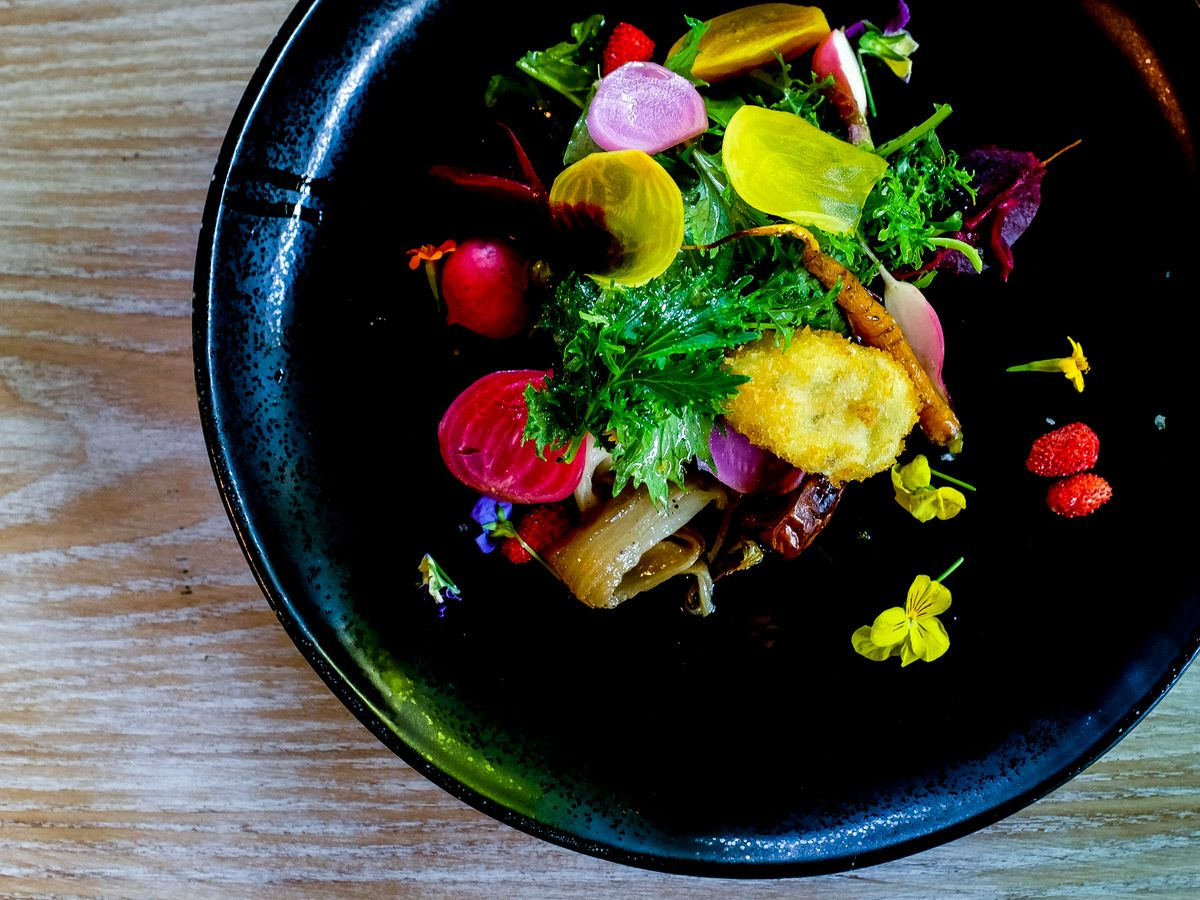 a salad with yellow and pink radishes in a black bowl